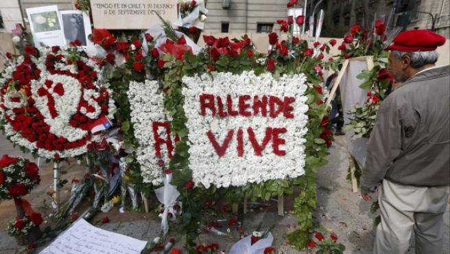 Un hombre observa las ofrendas florales bajo la estatua del presidente Salvador Allende junto al Palacio de La Moneda.