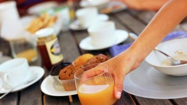 Una familia sentada a la mesa desayunando.