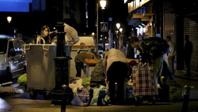Un grupo de personas busca en cubos de basura.