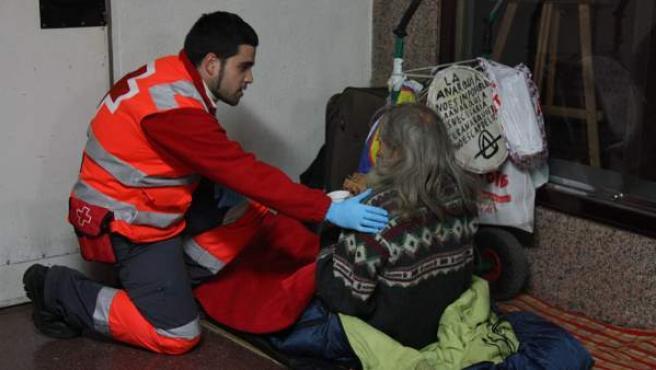 Un voluntari de Creu Roja entrega una beguda calenta, menjar i una manta a una persona sense llar.