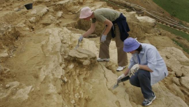 Dos personas trabajan en un yacimiento.
