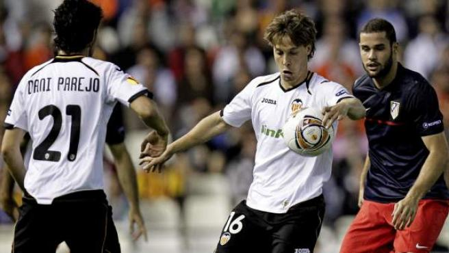 Sergio Canales, Dani Parejo y Mario Suárez pelean por un balón durante el Valencia - Atlético.