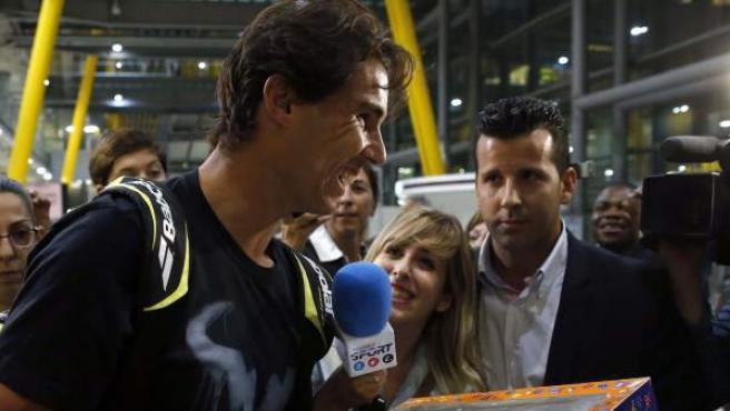 El tenista español Rafa Nadalc sostiene la tarta que le regalaron a su llegada al aeropuerto de Barajas, tras lograr su segundo Abierto de Estados Unidos. El tenista suma 13 grandes, uno menos que Sampras y cuatro que Federer.