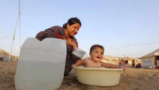Fotografía de una refugiada siria bañando a un niño en el campamento para refugiados Quru Gusik (Irak).