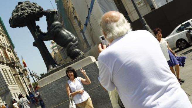 Dos turistas se hacen una foto con el Oso y el Madroño de la Puerta del Sol de Madrid.