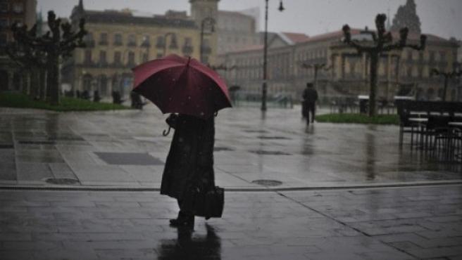 Una mujer camina bajo la lluvia con su paraguas.