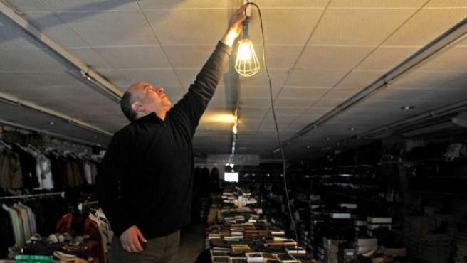 Un hombre instala una bombilla en un comercio de Barcelona.