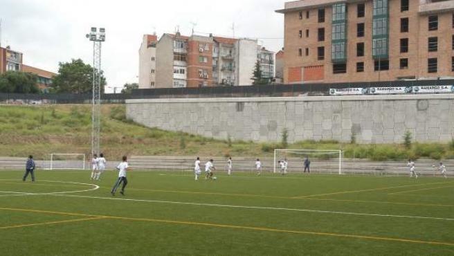 Varios chicos entrenan en uno de los campos de hierba artificial construidos por el Ayuntamiento de Madrid.