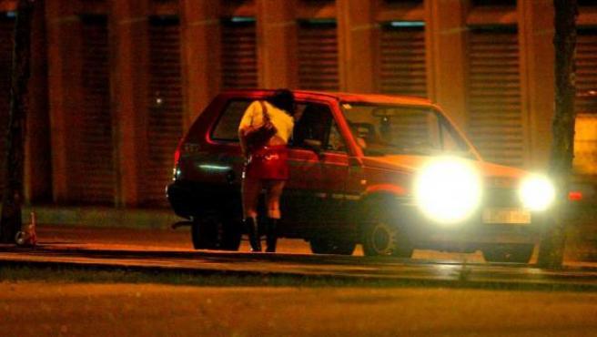 Una prostituta se acerca a un coche.
