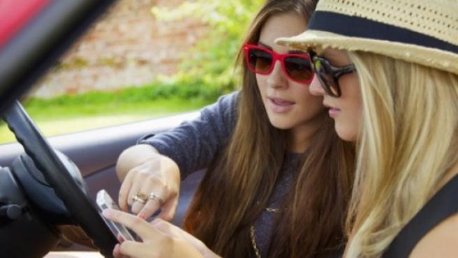 Dos jóvenes utilizan un smartphone.