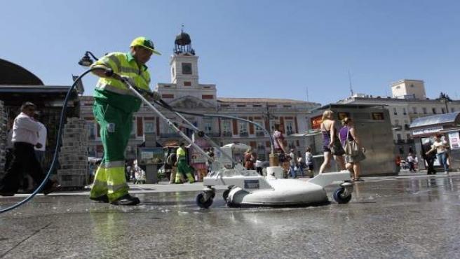 Un operario del Ayuntamiento de Madrid limpia el suelo de la Puerta del Sol.