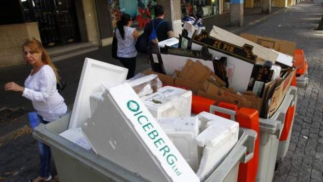 Vecinos de Madrid pasean junto a dos cubos de basura llenos de residuos, en la calle Francisco Silvela.