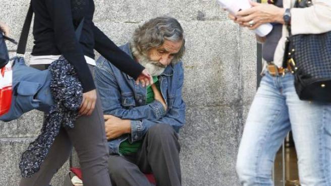 Un mendigo, sentado en una de las aceras de la Puerta del Sol, en Madrid.