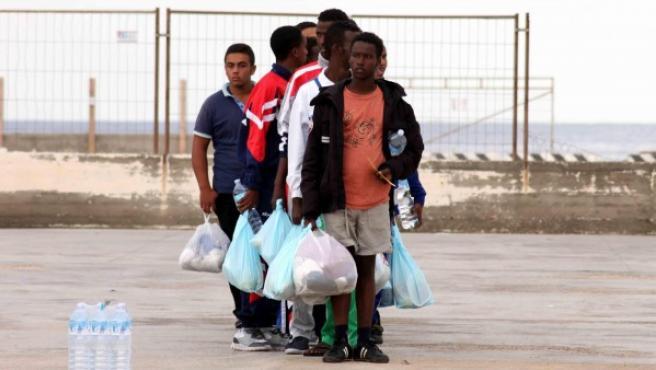 Un grupo de inmigrantes caminan por el puerto de Lampedusa (Italia).