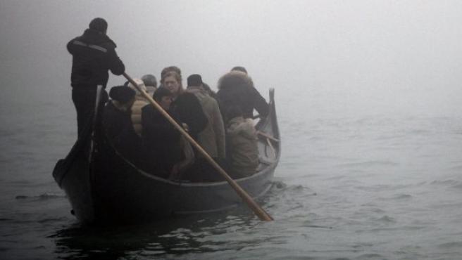 Un gondolero conduce a sus pasajeros a través del Gran Canal de Venecia, cubierto de niebla.