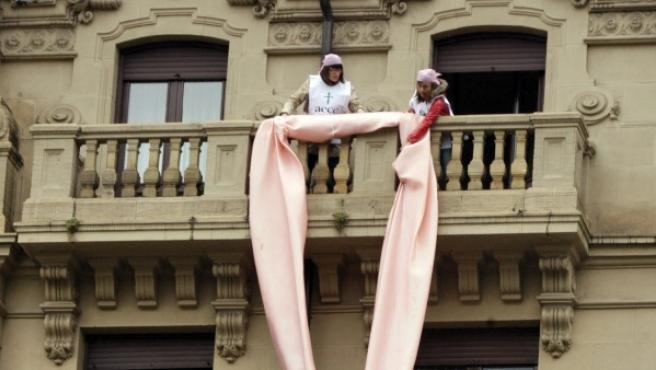 Imagen de archivo de dos mujeres de la Asociación Española contra el Cáncer (AECC) que colocan un lazo rosa en la sede de esta asociación en Bilbao.