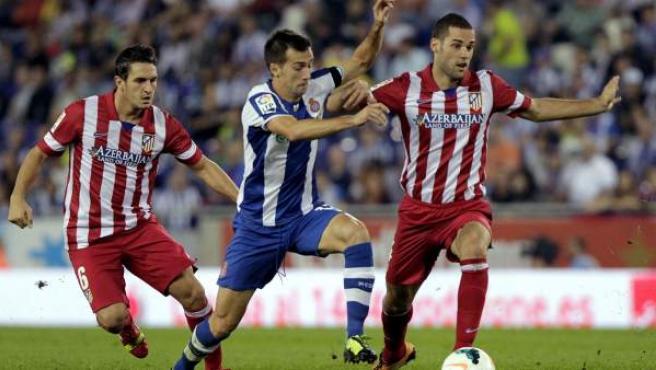 Los jugadores internacionales del Atlético de Madrid Koke Resurrección y Mario Suárez luchan un balón en el Espanyol-Atlético de Madrid.