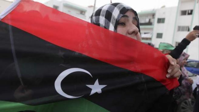 Una mujer porta la bandera de Libia en una manifestación en Misrata.