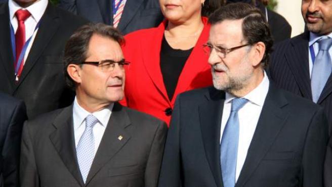 El presidente de la Generalitat, Artur Mas, y el del Gobierno, Mariano Rajoy, conversan con el semblante serio durante la foto de familia del I Foro Económico Mediterráneo.