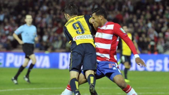 El delantero del Atlético de Madrid David Villa (i) cae tras la entrada del colombiano Jeison Murillo, del Granada CF.