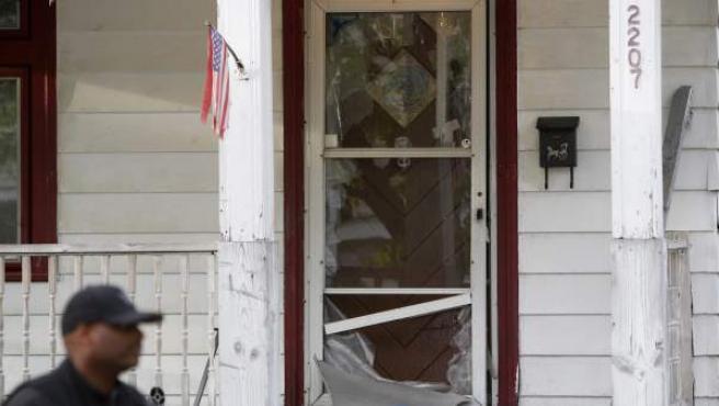 Un policía pasa junto a la puerta rota de una casa en la Avenida Seymour, en el barrio de Cleveland, Ohio (EE UU), donde fueron halladas tres jóvenes desaparecidas.