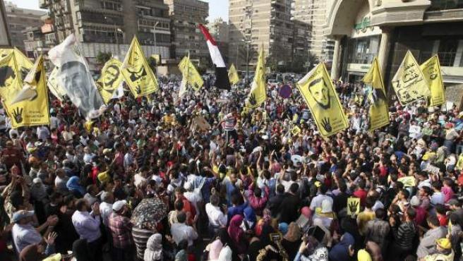 """Decenas de simpatizantes del depuesto presidente egipcio Mohamed Mursi muestran pancartas con el saludo de los """"cuatro dedos"""" durante unas protestas en El Cairo (Egipto)."""