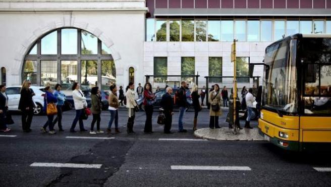 Cola de usuarios esperando el autobús en una jornada de huelga en Portugal.