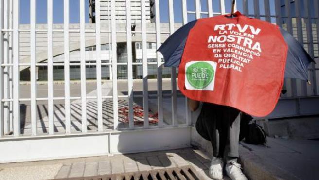 Un trabajador de RTVV se protege del sol, a las puertas del Centro de Emisiones de Burjassot, días después de que el presidente de la Generalitat, Alberto Fabra, anunciara su cierre.