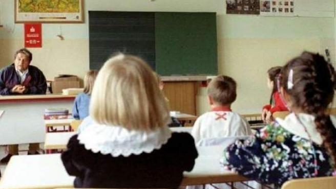 Un grupo de niños recibe clase en un aula.