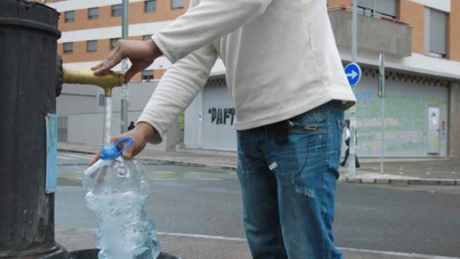 Uno de los inquilinos de La Utopía recoge agua de la fuente