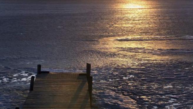 La capa de hielo que cubre el lago Elbsee comienza a derretirse a causa de las agradables temperaturas, en Aitrang (Alemania).