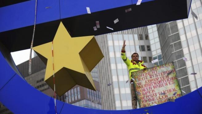 El agente inmobiliario Novak Petrovic, de pie encima del símbolo del euro, lanza panfletos bancarios falsos para llamar la atención sobre la complicidad de los bancos con la crisis financiera, en Fráncfort, Alemania.