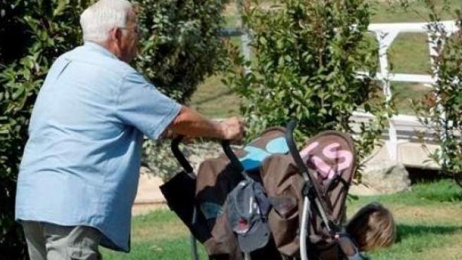 Imagen de archvio de un abuelo paseando junto a su nietos.