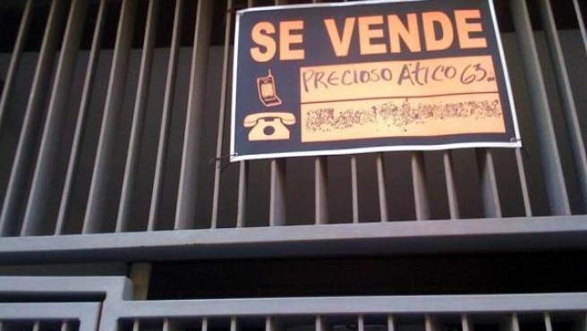 El cartel de Se Vende en el portal de un edificio de pisos.