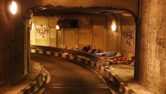 Boca del túnel de Santa Cruz de Marcenado, en el distrito Centro de Madrid, con varios sin techo durmiendo en su interior.