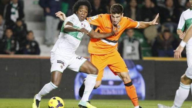 Carlos Sánchez, del Elche, pelea un balón con Antonio Barragán, del Valencia.
