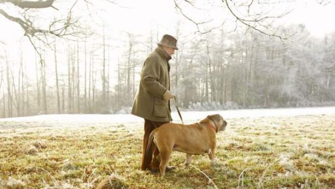 Imagen de un hombre paseando a su perro.