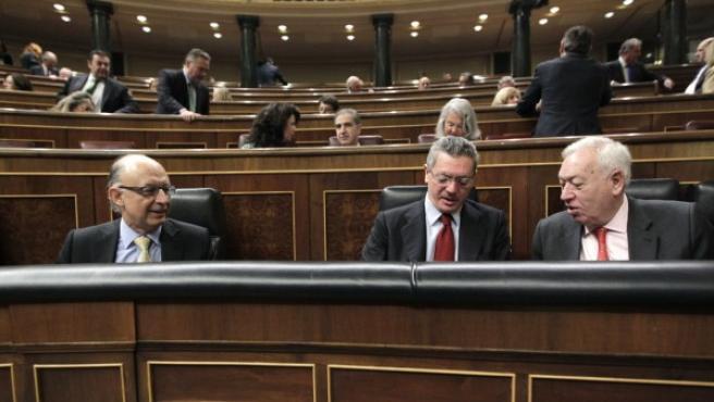 La vicepresidenta del Gobierno, Soraya Sáenz de Santamaría y los ministros de Justicia, Alberto Ruiz-Gallardón (i) y Exteriores, José Manuel García-Margallo, al inicio de una sesión de control al Ejecutivo.