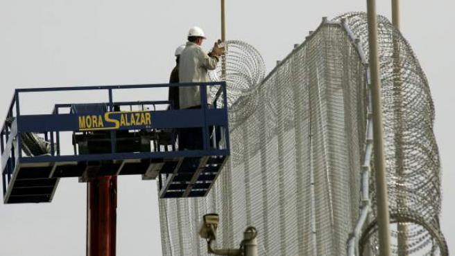 Trabajadores colocando nuevos alambres en la valla que separa Melilla y Marruecos.