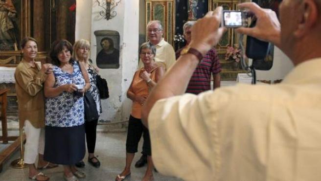 Un grupo de turistas de Valencia y Francia se fotografían ante la imagen del eccehomo en la capilla del Santuario de la Misericordia, en la localidad zaragozana de Borja.