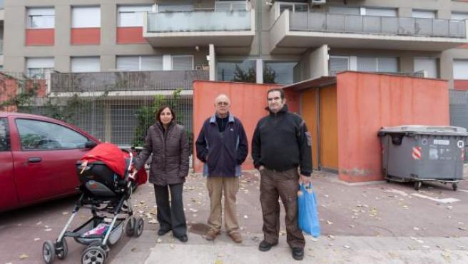 Tres dels veïns que no poden afrontar el pagament de la hipoteca del pis social des que els han suprimit l'ajut estatal, davant de casa seva.