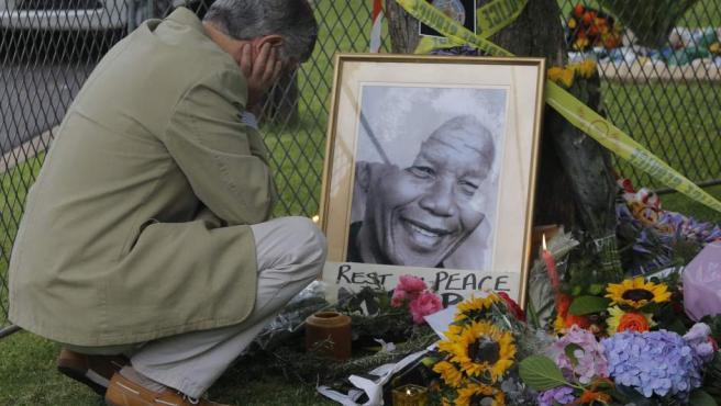 Un hombre llora junto a una fotografía del expresidente sudafricano Nelson Mandela frente a su última residencia en Sudáfrica.