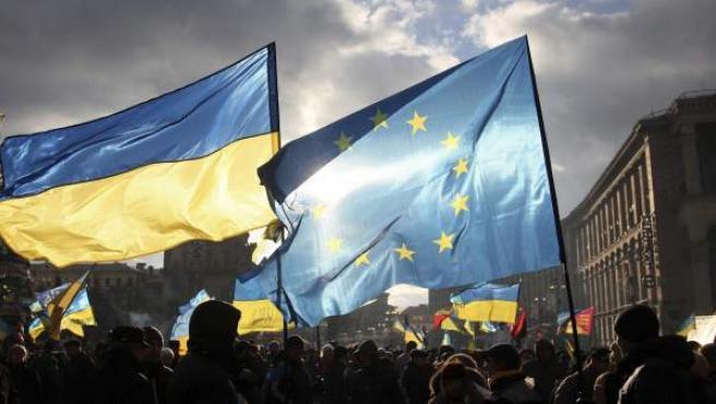 Varias personas ondean banderas ucranianas y de la Unión Europea (UE), durante una concentración a favor de la integración de Ucrania en la UE.