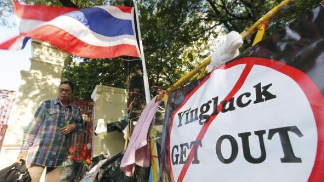 Un manifestante tailandés junto a una pancarta contra la primera ministra del país, Yingluck Shinawatra.