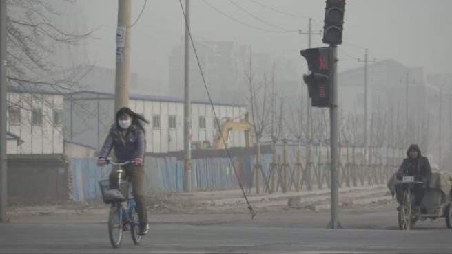 Dos ciudadanos chinos pasean en bicicleta por Pekín (China).