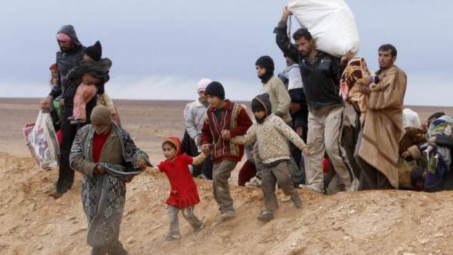 Un grupo de refugiados sirios llegan al este de la frontera entre Siria y Jordania, tratando de huir de la violencia en su país para buscar una mayor seguridad.