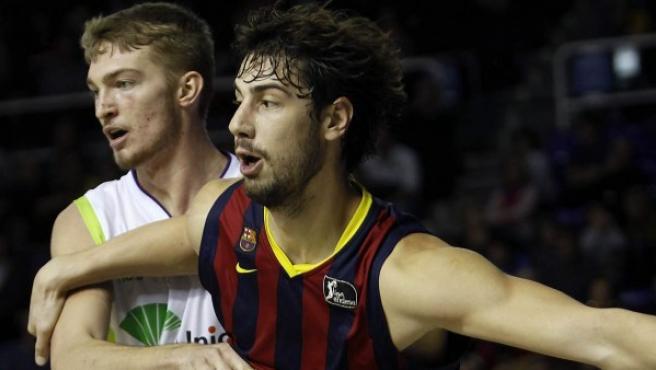 El pivot croata Barcelona, Ante Tomic (d), lucha por la posición con el lituano Domas Sabonis (i), de Unicaja.