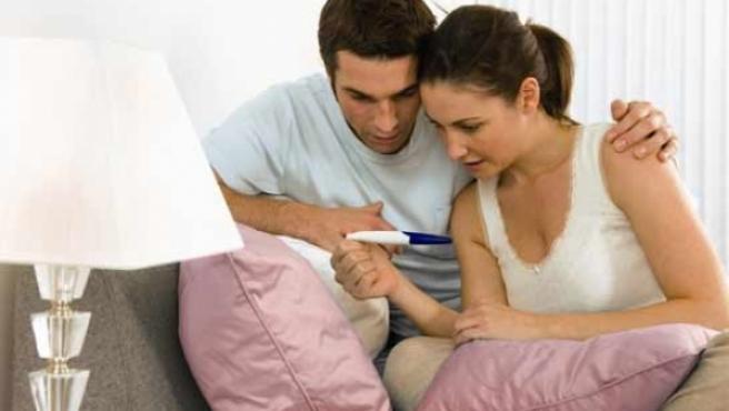 Una pareja observa el resultado de un test de embarazo.