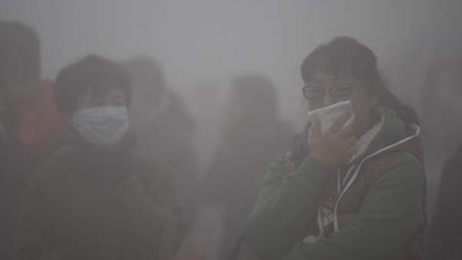Dos mujeres se protegen con mascarillas de la fuerte capa de esmog (mezcla de humo y contaminación) en el noreste de China.