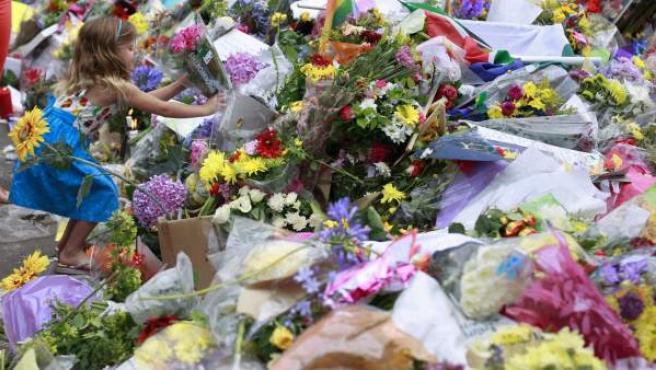 Una niña deposita un ramo de flores en el exterior de la casa del expresidente sudafricano Nelson Mandela en Johannesburgo, Sudáfrica.